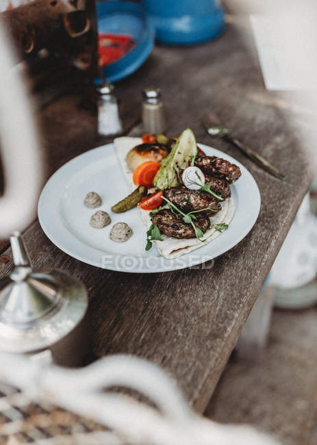 Arabic meat kebab plate with vegetables on plate on wooden table — Stock Photo