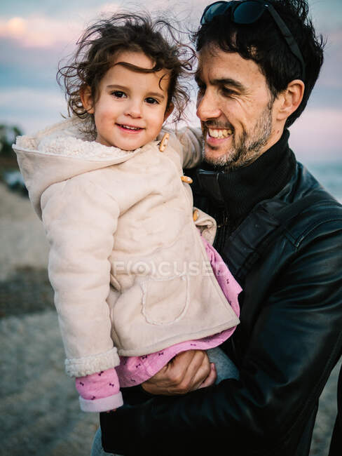 Cute scene of dad holding and hugging her little daughter at the beach in winter — Stock Photo