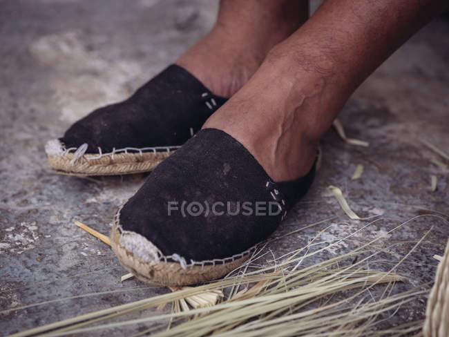 Pés de artesão anônimo em sapatos rasgados no chão grungy perto de folhas de palma secas — Fotografia de Stock