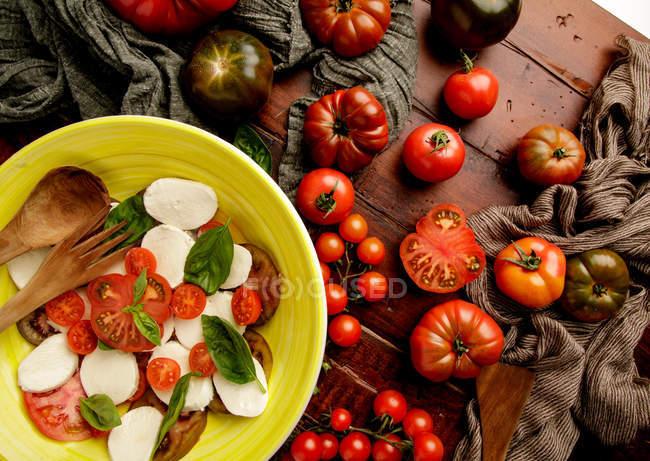 Tomates maduros frescos em mesa de madeira perto de tigela de salada Caprese gostosa — Fotografia de Stock