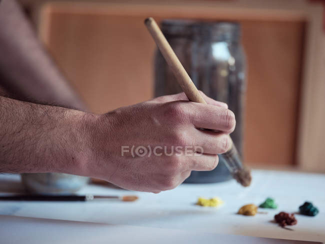 Closeup hand of anonymous artist with paintbrush drawing picture on canvas in studio — стокове фото