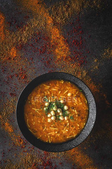 Traditionelle Harira-Suppe für Ramadan in schwarzer Schüssel auf dunkler Oberfläche mit verstreuten Gewürzen — Stockfoto