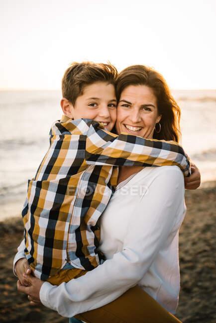 Mujer de mediana edad con su hijo en la orilla del mar sonriendo y abrazándose - foto de stock