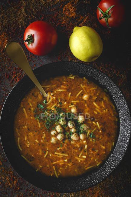Traditionelle Harira-Suppe für Ramadan in schwarzer Schüssel auf dunkler Oberfläche mit Zutaten — Stockfoto