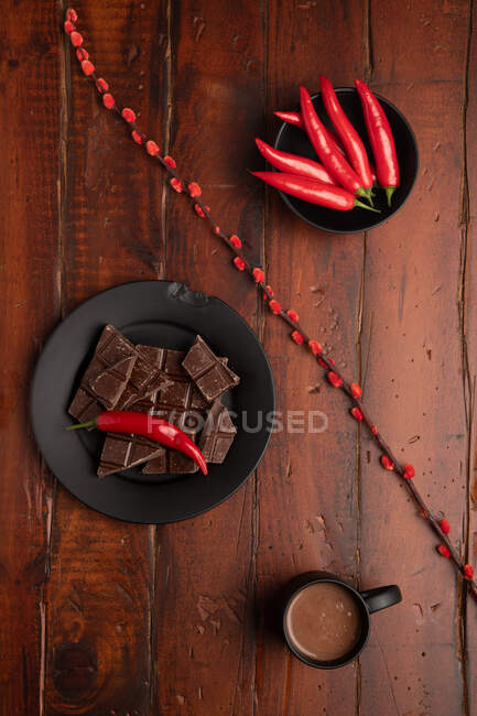 Mug of fresh hot drink placed on lumber tabletop near plate with pieces of chocolate and chili pepper — Stock Photo