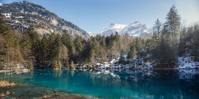 Landscape of peaceful azure lake with snowy shore and resort building in mountains of Switzerland — Foto stock