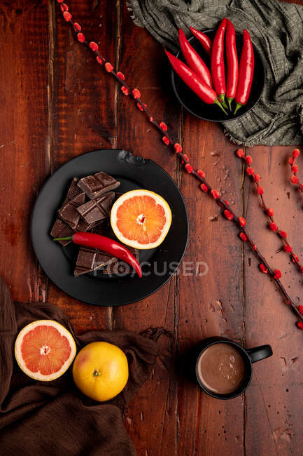 Mug of tasty hot chocolate placed on timber tabletop near assorted desserts and fruits for breakfast — Stock Photo