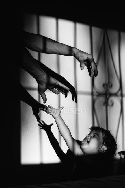 Black and white image of an anonymous father playing with shadows at home with his kid — Stock Photo