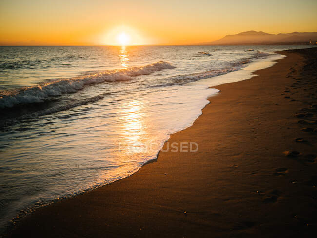 View from the coast to orange sunset in cloudy sky over the ocean. — Stock Photo