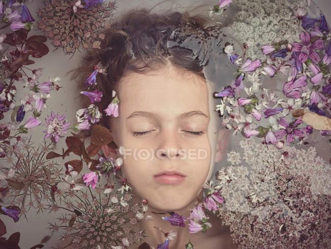 Dall'alto faccia di bambino in liquido tra petali freschi di fioriture — Foto stock