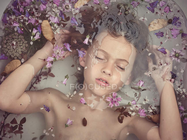From above face of child in liquid between fresh petals of blooms — Stock Photo