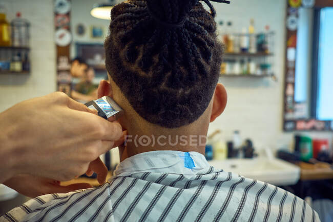 Crop vista da dietro di parrucchiere anonimo facendo un taglio di capelli moderno con un rasoio a un cliente afro-americano senza volto — Foto stock