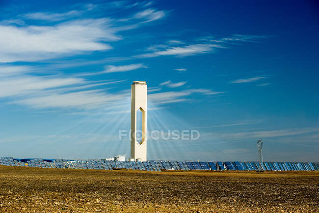 Tall tower in photovoltaic power station under blue sky with clouds — Stock Photo