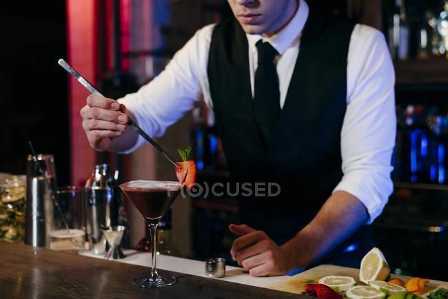 Giovane elegante barman che lavora dietro un bancone del bar preparando un drink in un bicchiere — Foto stock