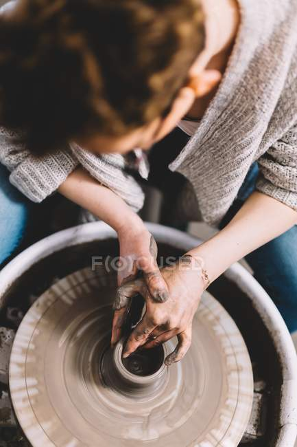Female potter with dirty hands making clay pot on wheel in workshop — Stock Photo