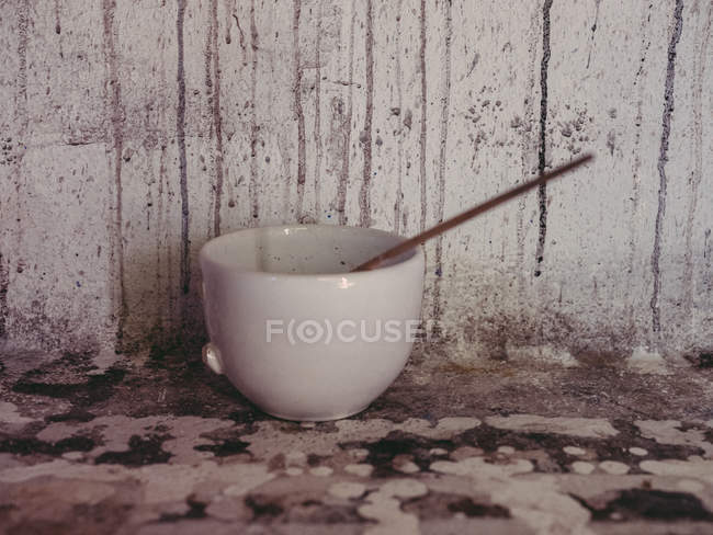 Broken ceramic cup with thin paintbrush near grungy wall in artist workshop — Stock Photo