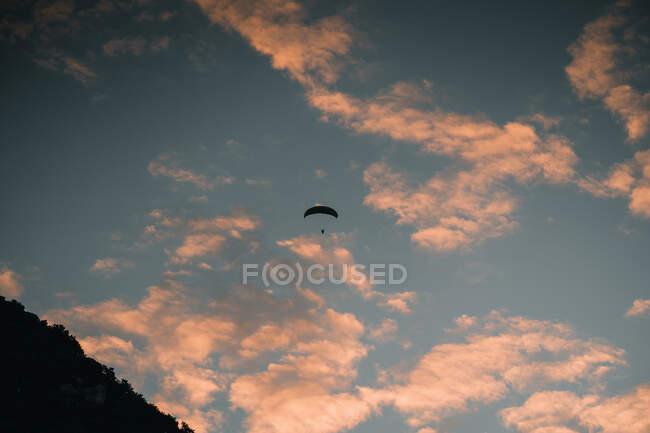Силуэт дальнего парашюта, летящего против облачного закатного неба на горе Маунгануи, Новая Зеландия — стоковое фото