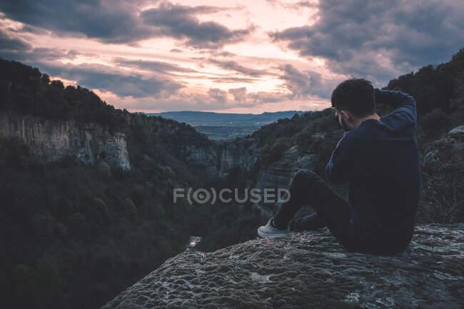 Hombre con cámara de fotos sentado en la montaña de la colina con magnífica puesta de sol - foto de stock