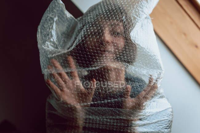 Mujer mirando a la cámara mientras enredada en una envoltura de burbujas - foto de stock