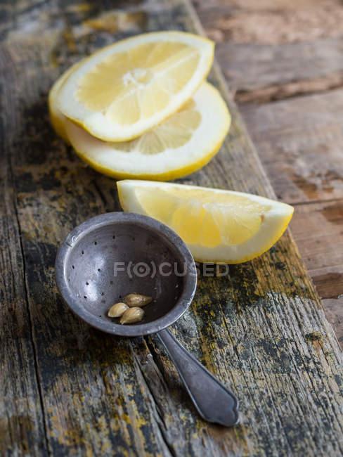 Primer plano de rodajas de limón y colador de metal viejo en tablero de madera - foto de stock