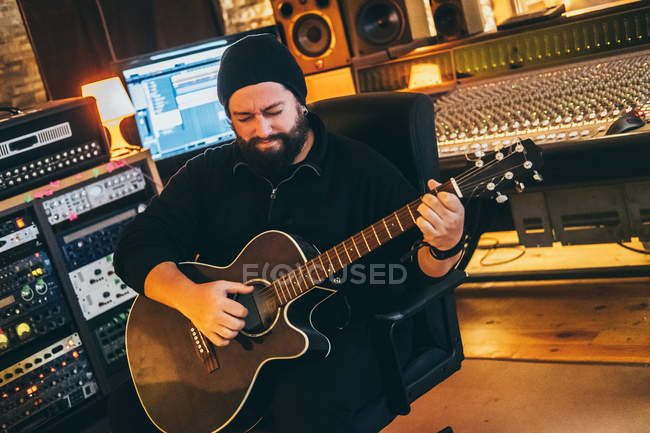 Erwachsener Mann sitzt im Musikstudio und spielt Gitarre — Stockfoto