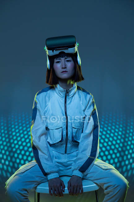 Junge Frau mit Virtual-Reality-Brille sitzt auf einem Stuhl und blickt mit Neonlicht in die Kamera — Stockfoto