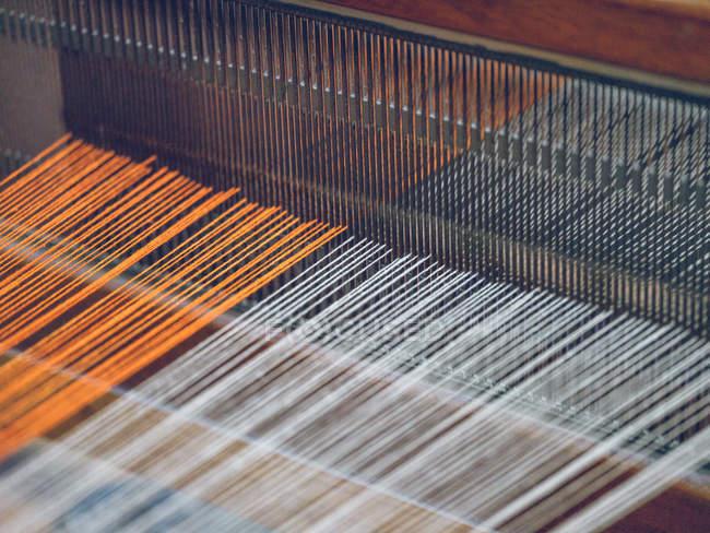 Linhas do algodão da cor alaranjada e branca no tear industrial na fábrica da tela — Fotografia de Stock