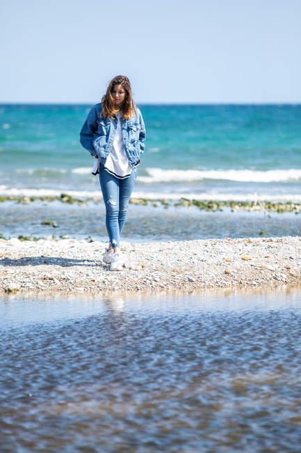 Giovane donna che cammina sulla riva del mare — Foto stock
