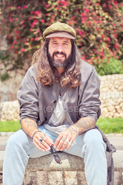 Stylish bearded man with long hair sitting in park — Stock Photo