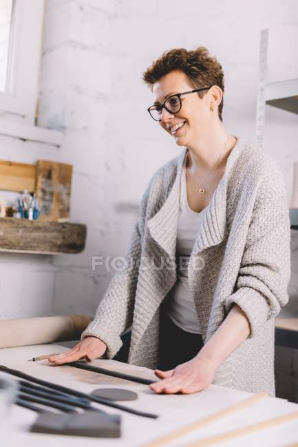 Female potter using clay strips to shape pot on workbench in professional workshop — Stock Photo