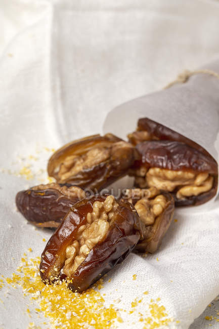 Halal snack for Ramadan with dried dates and walnuts on white cloth — Stock Photo