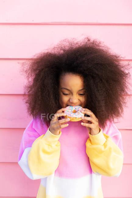 Афроамериканець дівчина кусає пончик з задоволенням проти рожевої стіни — стокове фото