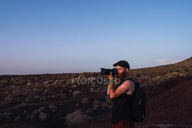 Side view of traveling man with backpack taking photo of landscape in dusky desert, Spain — Stock Photo