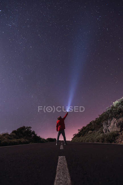 Traveler standing with torch at starry night on road in countryside — Stock Photo
