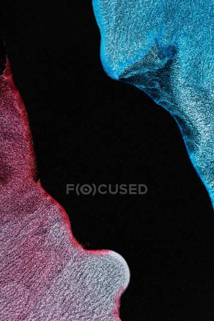 Verschüttete bunte metallische Farbstoffe mischen und verteilen sich auf schwarzem Hintergrund — Stockfoto