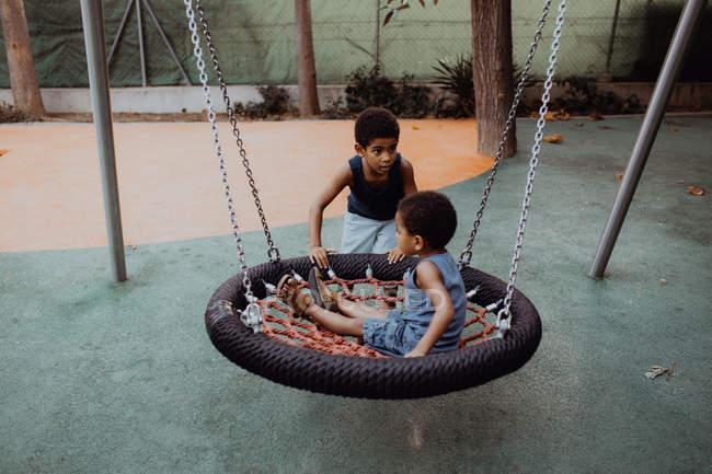 Афроамериканский мальчик смотрит в сторону и толкает качели с маленьким братом, играя вместе на детской площадке — стоковое фото