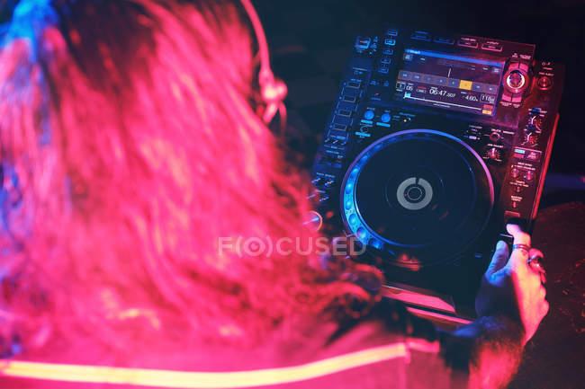 Anonimo dj man giocare in un club con le luci — Foto stock