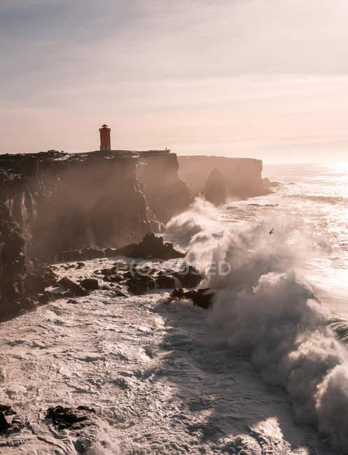 Ondas da tempestade na costa ocidental de Islândia e do farol de Svrtuloft no por do sol — Fotografia de Stock