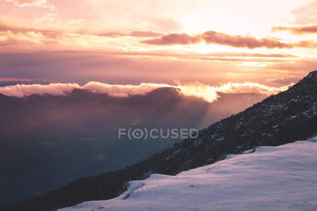 Sun setting over snowy mountains — Stock Photo