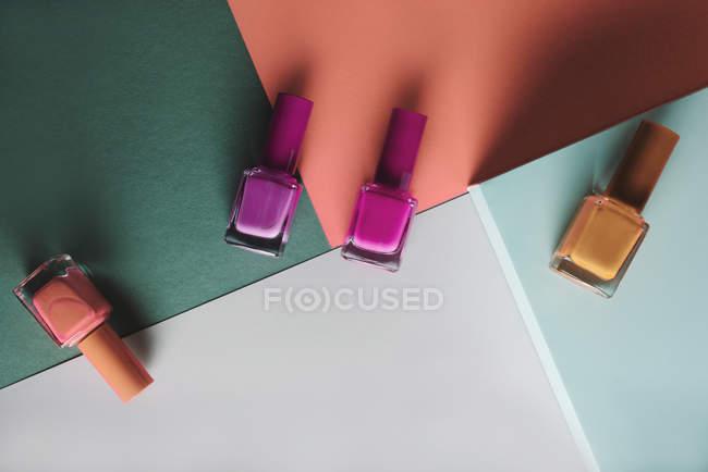 Smalti per unghie multicolori su sfondo modello geometrico colori — Foto stock