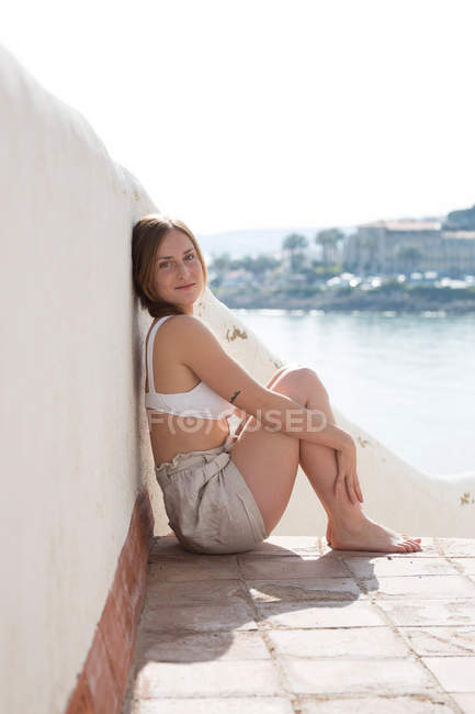 Smiling woman relaxing near plaster railing on sea coast — стоковое фото