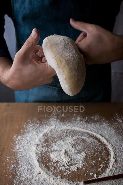 Cocinero masculino irreconocible dando forma a masa fresca con harina mientras cocina Rosca de Reyes sobre mesa de madera en la cocina . - foto de stock