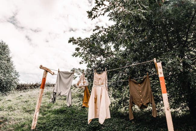 Vintage clothes hanging on ropes and drying on grassy hillside against cloudy sky in Mount Maunganui, New Zealand — Stock Photo