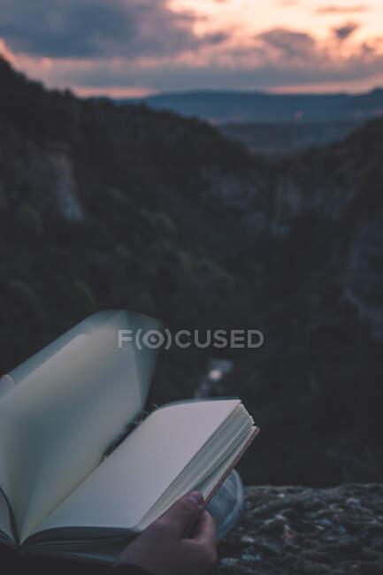 Подивіться на маленьку ріку в каньйоні і на ноги людини з книгою сидячи на краю — стокове фото