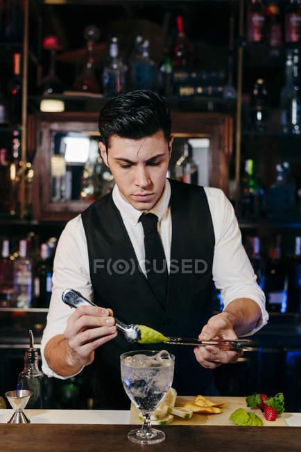 Giovane elegante barman che lavora dietro un bancone del bar mescolando bevande con frutta — Foto stock