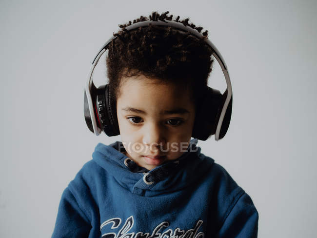 Sweet African American boy in trendy sweatshirt listening to music in headphones while standing against gray background — Stock Photo