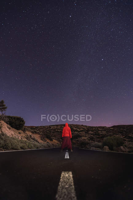 Traveler standing on empty road at night — Stock Photo