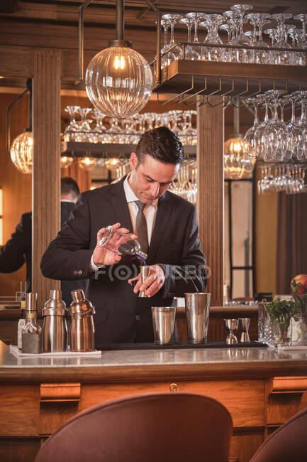 Cantinero en elegante traje vertiendo licor en taza de medir mientras prepara cóctel en el bar del restaurante de lujo - foto de stock
