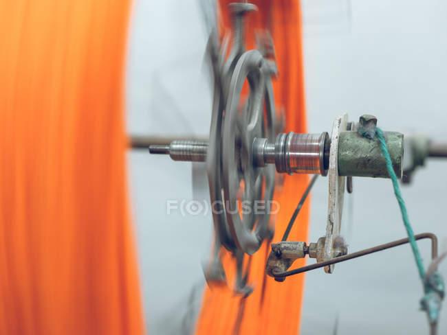 Orange thread spinning on machine on factory — Stock Photo