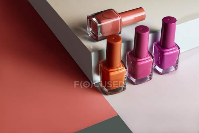 Mehrfarbige Nagellacke auf geometrischem Hintergrund — Stockfoto